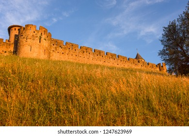 France, Carcassonne: Panorama front view of famous Cite de Carcassonne in the afternoon in the city center with high exterior wall, battlements and blue sky - concept travel history medieval castle