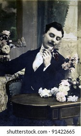 FRANCE I CIRCA 1903: A postcard printed in France shows Man considers flowers sitting at the table, circa 1903
