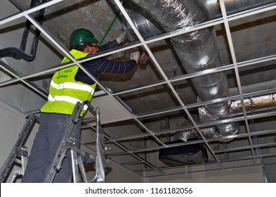 Besançon, France - February 16, 2015: Worker installing ductworks under a suspended ceiling on a construction site.