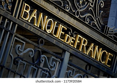 Besançon, France - February 17, 2008: Low angle view of the wrought iron gate of the Bank of France building with the golden letters of the signboard lit by the sun.