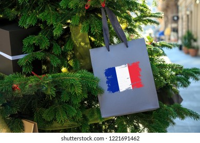 France flag printed on a Christmas shopping bag. Close up of a shopping bag as a decoration on a Xmas tree on a street in France. Christmas shopping, local market sale and deals concept.