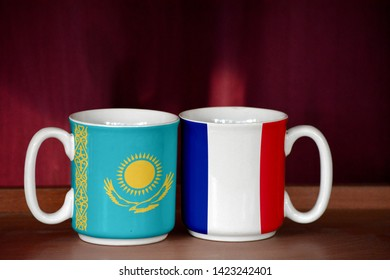 France and Kazakhstan flag on two cups with blurry background
