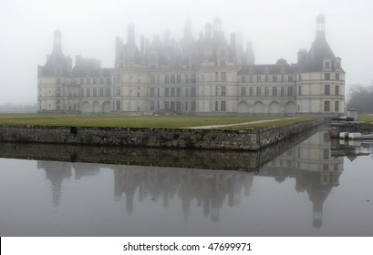 France. Loire Valley. View on Chambord castle across the pond in winter fog