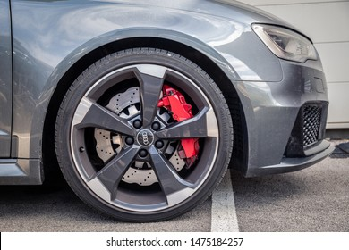 France Lyon 2019-06-20 closeup wheel premium sports car dark gray hatchback Audi RS 3, low profile tires, brand logo on cast disk, red caliper car produced by German automobile manufacturer Audi AG