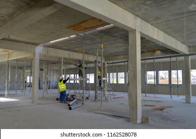 Besançon, France - March 18, 2014: Workers installing ductwork among struts in an empty room on a construction site.