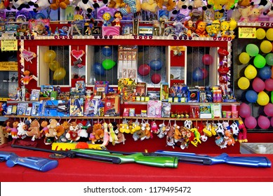 Besançon, France - March 29, 2008: Colorful shooting game stand in a funfair with lead rifles and balloons among a bunch of toys to win.