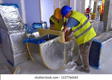 Besançon, France - May 21, 2014: Workers installing a ventilation duct on a construction site.