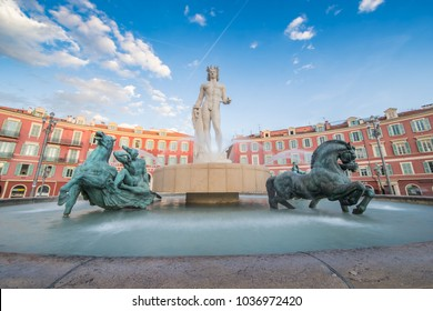 France, Nice, 15 May 2017: Fountain of the Sun, Place Massena in center of Nice, Plassa Carlou Aubert, tourism, sunny day, blue sky, square tiles laid out in a checkerboard pattern, Apollo statue