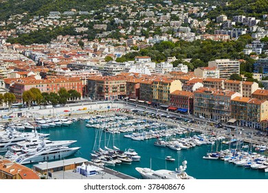 France, Nice, 15 September 2015: Port of Nice, Corsica ferry yellow, azure water, luxury yachts, small boats colored, red roofs, aerial view, french riviera