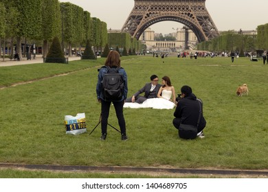 France, Paris, 2019/04, Couple pose for wedding photographs in front of the The Eiffel Tower which is the second tallest free-standing structure in France.