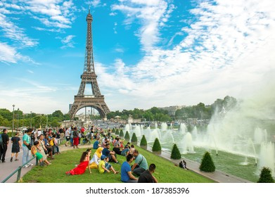 FRANCE, PARIS - AUGUST 23, 2013: many tourists sitting near famous Eiffel Tower and enjoying the evening