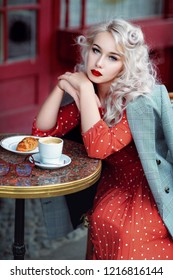France, Paris, a beautiful retro girl blonde in a red dress with polka dots is siting in a cafe. Pin up art.