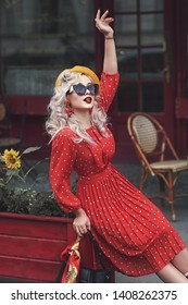 France, Paris, a beautiful retro girl blonde in a red dress with polka dots and a yellow beret is siting in a cafe.