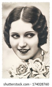 FRANCE, PARIS - CIRCA 1920: portrait of young woman with rose flowers. Retro style make up and hair look