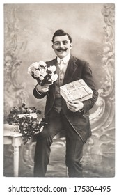 FRANCE, PARIS - CIRCA 1920: portrait of young man with rose flowers and gift. Typical for this period mans look. Congratulations. Valentines Day. Birthday