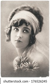 FRANCE, PARIS - CIRCA 1920: portrait of young beautiful woman with flowers. Typical for this period womans look. Original film and paper grain