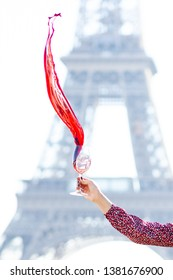 France, Paris, Eiffel tower. Young girl in red dress is holding a glass of red wine in her hand. Wine is pouring from the glass as flame. Historical building on background
