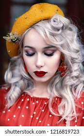 France, Paris, portrait of beautiful blond girl in a red dress with polka dots and a yellow beret.