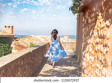 France, Provence medieval town Roussillon. Pretty young woman  in blue dress walking down the street in Provencal old city.  Travel and wanderlust concept. June - time of blooming lavender in Provence