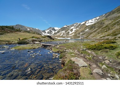 France Pyrenees mountain landscape, stream and Trebens lake with Carlit massif in background, natural park of the Catalan Pyrenees