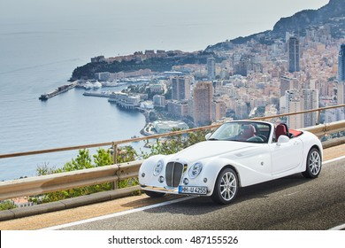 France, Roquebrune, 7 April 2016: The vintage cabriolets gold and white color stand  at an observation deck hotel Vista overlooking a panorama of Monaco, Monte-Carlo at sunny day, skyscrapers