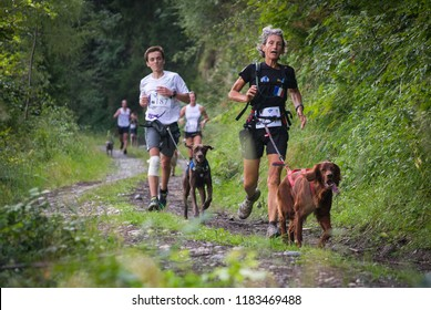 FRANCE, SAINT COLOMBAN DES VILLARDS. AUGUST, 2015: Competitors Running with Dogs on the Forest Path in Rhones Alpes, Trophee des Montagnes, The Hardest Canicross Race.