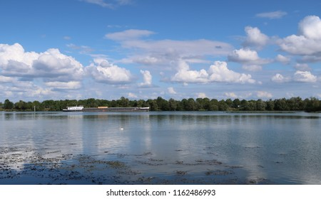 Mâcon, France – September 15, 2017: photography showing a barge on the Saône river. The photography was taken from the street of the city of Mâcon, France.
