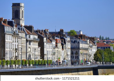 Besançon, France - September 4, 2018: Facades of old buildings on Quai Veil Picard with the bell tower of Église de la Madeleine behind.