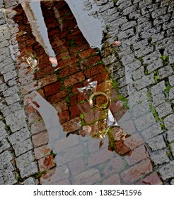 France, Strasbourg - June 2015: Saxophone player from walking jazz band reflected in puddle