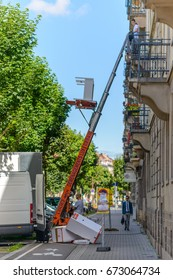 France, Strasburg 23 June 2016:Haulers delivering or collecting furniture from an upstairs apartment using a mechanical lift or hoist during removals viewed from the street in an urban environment