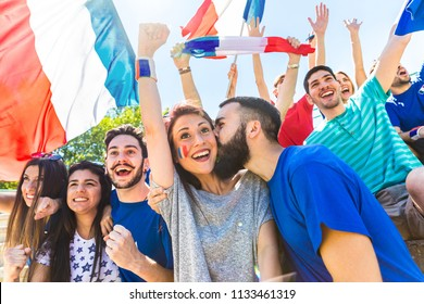 France supporters celebrating at stadium with flags. Couple kissing in the crowd of fans watching a match and cheering team France. Sport and lifestyle concepts.