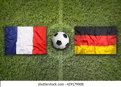 France vs. Germany flags on a green soccer field