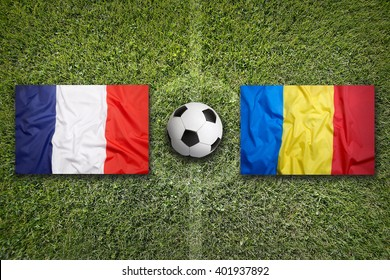 France vs. Romania flags on green soccer field