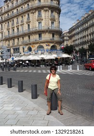 FRANCE-SEPTEMBER: A senior female tourist is seen with beautiful architecture of  La Samaritaine brasserie restaurant on main street of port city of Marseille in ca. September 2017.