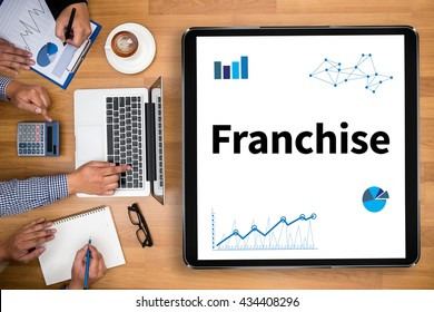 Franchise Business team hands at work with financial reports and a laptop
