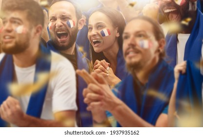 Francian football, soccer fans cheering their team with a blue scarfs at stadium. Excited fans cheering a goal, supporting favourite players. Concept of sport, human emotions, entertainment.