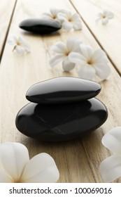 frangipani flower and black stone, zen spa on wood