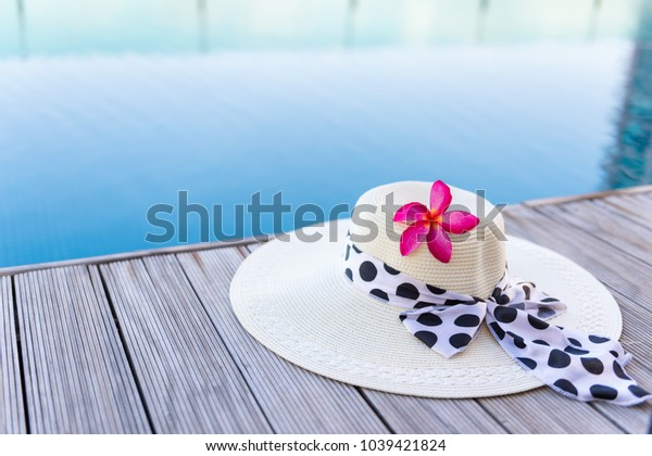Frangipani Flower and Straw Hat on Terrace Swimming Pool, Beauty Plumeria Flower With Women Hat Beside Poolside. Summer Holiday on The Beach and Relaxation Place, Vacations on Tropical Sea.