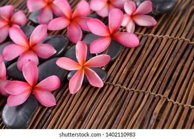 frangipani ,plumeria with black stones on bamboo black mat