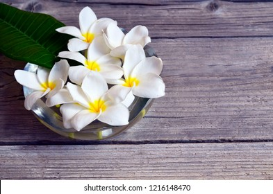 Frangipani (Plumeria) flowers in a glass bowl on old wooden background. Relaxing time or Spa concept with space for text.Selective focus.