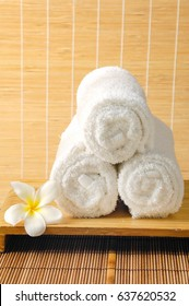 Frangipani with three rolled towel –mat background