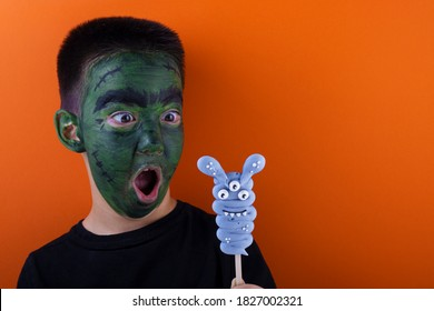 Frankenstein boy and a blue marshmallow on a stick. the concept of Halloween. creative idea
