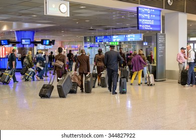 Frankfurt, Germany- 26 November 2015:Passengers queuing up with their luggage to check in at an airport departures terminal viewed from behind in a travel concept