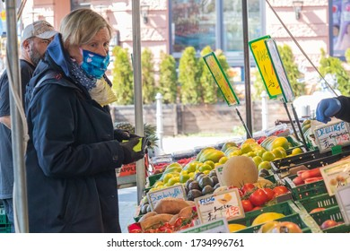 FRANKFURT, GERMANY - Apr 04, 2020: A person wearing a mouth protection buys fruit at market in Frankfurt Bockenheim during the Corona Virus Crisis.
