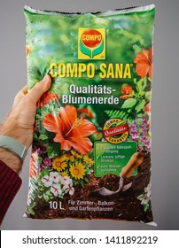 Frankfurt, Germany - Apr 22, 2019: Man hand holding against gray background package of COMPO SANA Qualitats-Blumenerde quality soil for indoor outdoor plants