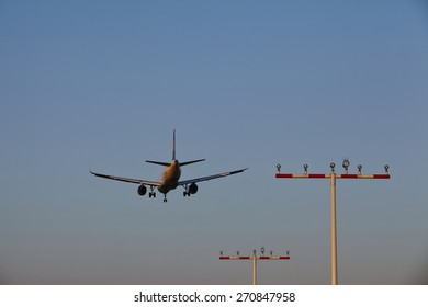 FRANKFURT, GERMANY - APRIL, 18. A plane over some beaconing masts approaches the airport of Frankfurt Main (Germany) in the evening on April 18, 2015.