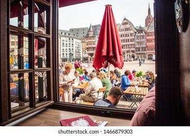 FRANKFURT, GERMANY - APRIL 23, 2019:  View of people dining outdoors in the altstadt römerberw as seen through a window.