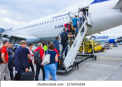 Frankfurt, Germany - April 28, 2018: The people boarding the Lufthansa Airline aircraft. Passenger walking to the rear entrance of airplane