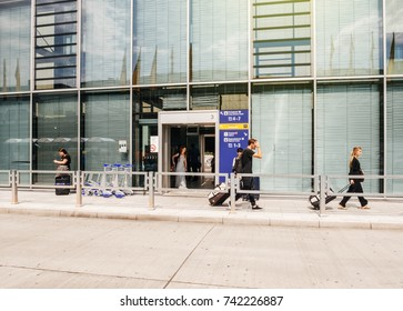 FRANKFURT, GERMANY - AUG 1, 2017: Young female and male passengers arriving with luggage at Frankfurt airport