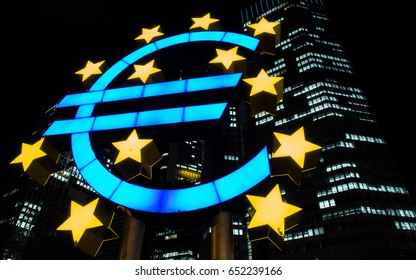 FRANKFURT, GERMANY - CIRCA JUNE 2017: Neon Euro currency symbol behind European central bank (ECB) at night in nasty weather